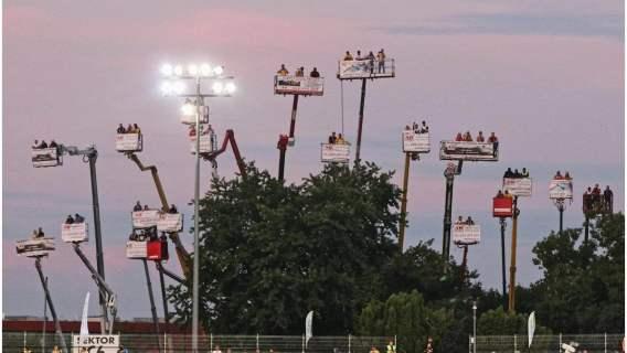 Kibice wynajęli dźwigi, aby wziąć udział w sportowym wydarzeniu.