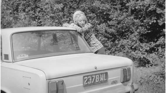 Grażyna Rutowska pozuje przy samochodzie Fiat 125 p na poboczu drogi.
