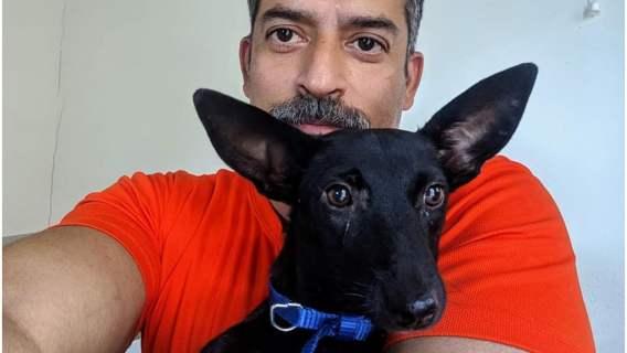 Rakesh Shukla z jednym z psów, które zamieszkały na jego działce.